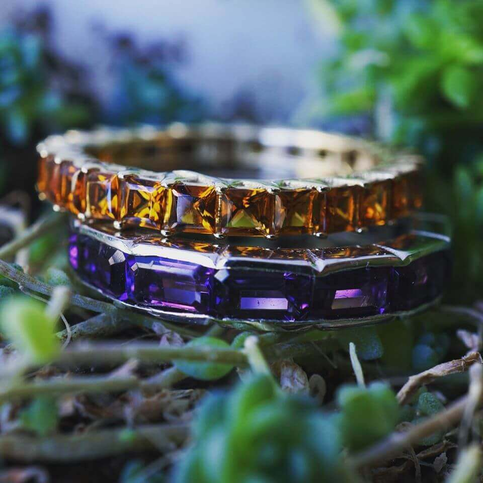 An amethyst eternity ring and a citrine eternity ring