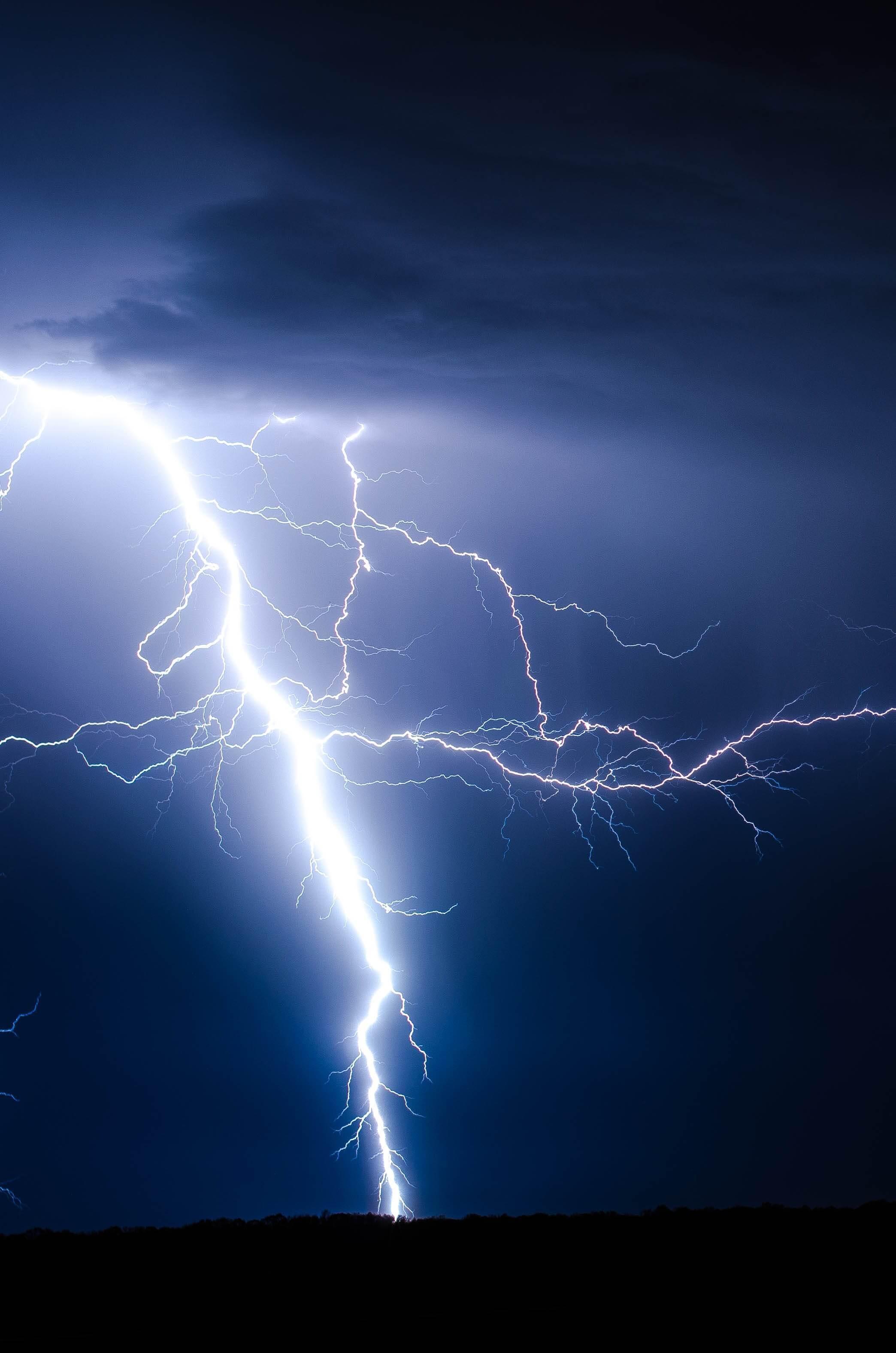 A bolt of lightning against a dark-blue sky.