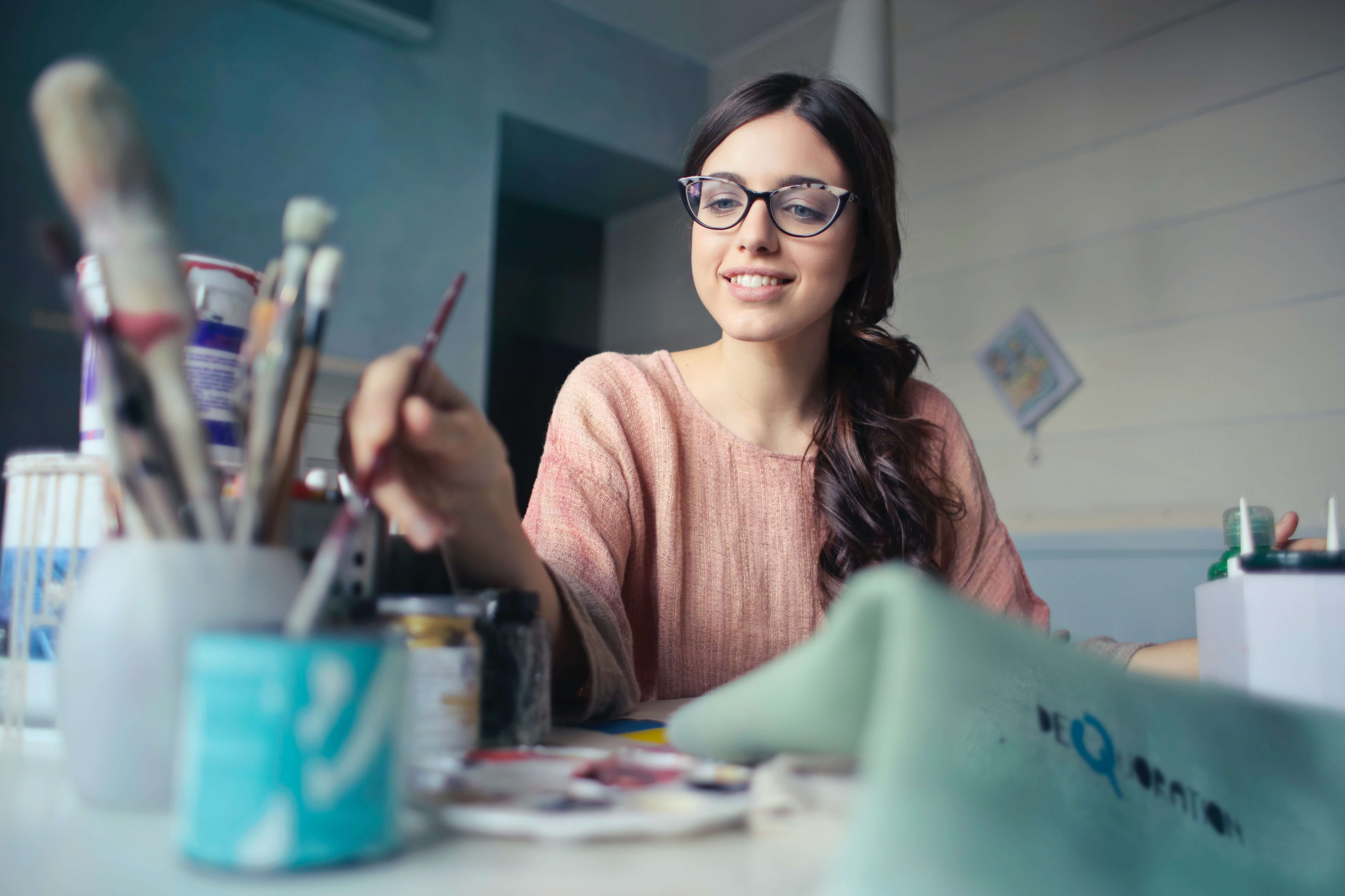 A woman with glasses holding a paintbrush.