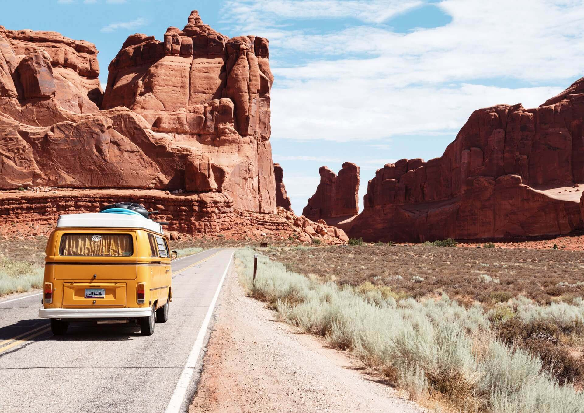 A yellow Volkswagon on a road near orange rock formations
