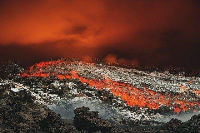 A dark cloudy red sky above lava and rocks.